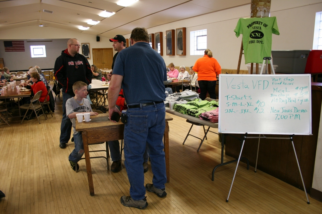 That's Vesta firefighter Neal Hansen to the left behind the table, photographed at the Vesta Fire Department  Pork Chop Feed in March.