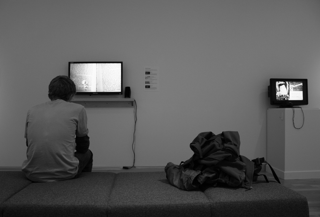 "A student studies a portion of ""The Intersection Between Book, Film, and Visual Narrative"" in the Kaemmer Family Gallery."