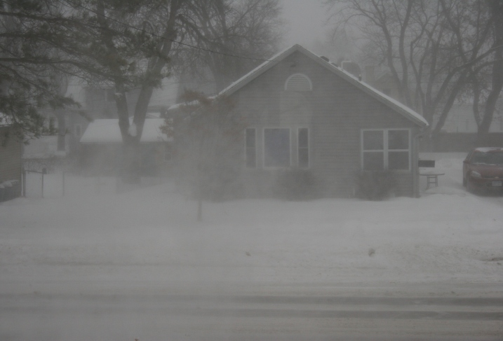 A view from my front window around 4:30 p.m. shows reduced visibility due to blowing snow and fresh snow falling.