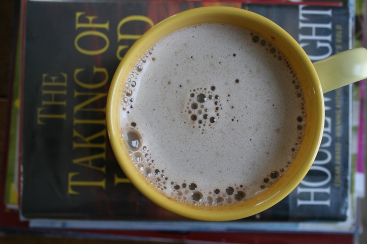A cup of instant cappuccino set atop a stash of books.