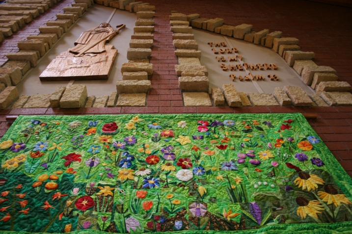 "The beautiful and stunning floral quilt art by Kevin Kreger is displayed below a wood carving by noted Faribault artist Ivan Whillock. Kreger coordinated the ""Consider the Lilies"" floral display at Trinity."