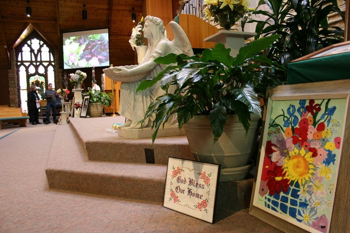 Flower art buffeted both sides of the chancel, here near the baptismal font and pulpit.