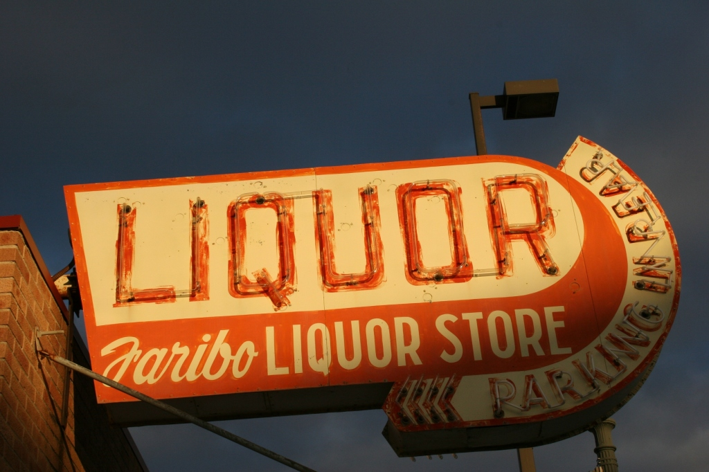 The setting sun spotlights vintage Faribo Liquor Store signage along Fourth Street/Minnesota Highway 60 in downtown Faribault. Minnesota Prairie Roots file photo 2009.