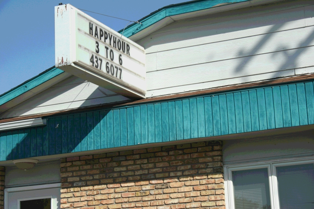 In Vermillion, near Hastings, a bar advertises the ever popular happy hour. Minnesota Prairie Roots file photo 2012.