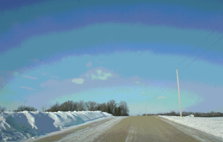 A ridge of plowed snow edges a country road near Montgomery, Minnesota.