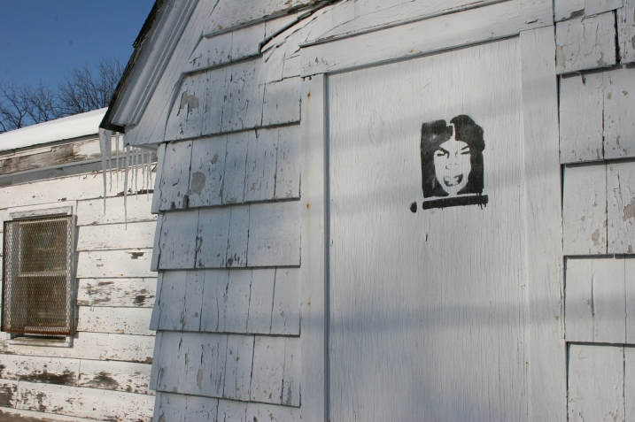 Why is this face painted on a door of the building where the tow truck is parked? And whose face is this?