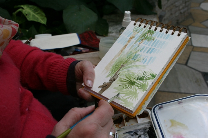 Watercolor artist Kathleen Richert paints a fountain in the Palm Dome.