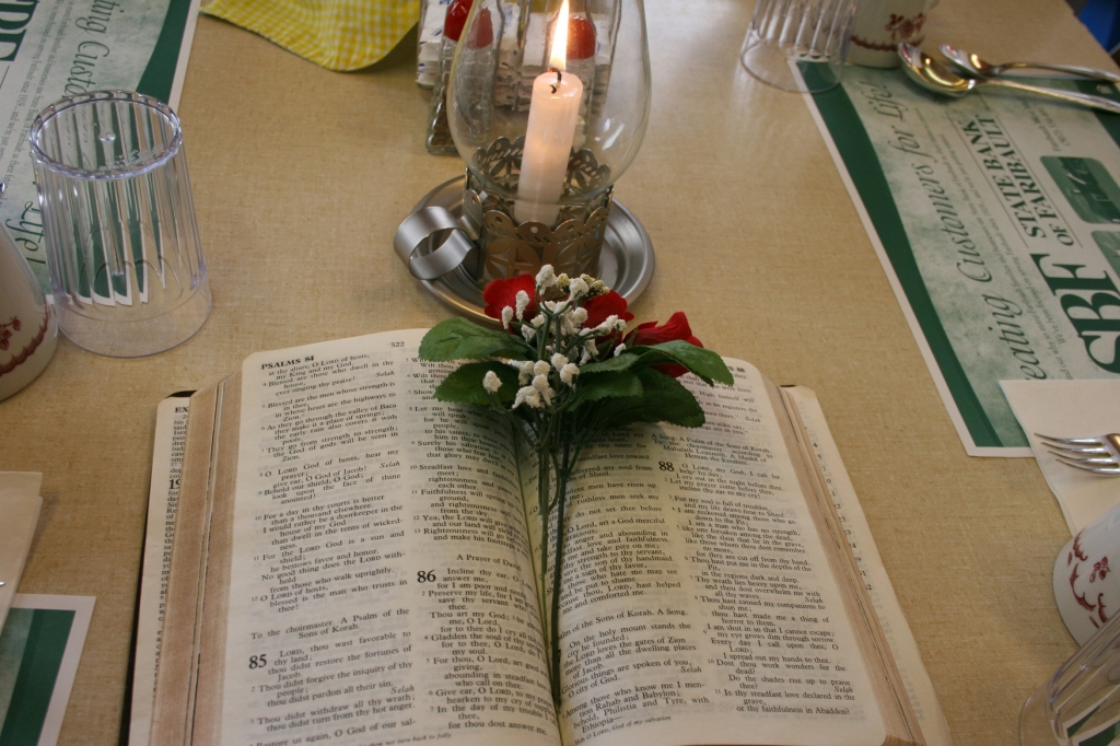 Bibles, florals and candles  decorated tables.