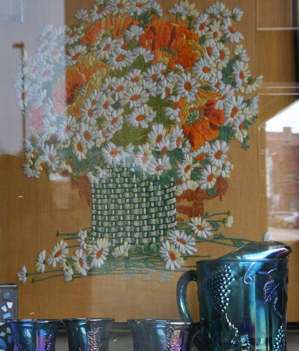 This crewel embroidery art, crafted by the same woman who created the floral I purchased, now hangs in the front window of the Nook & Cranny.
