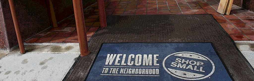 Remember to shop local as noted in this mat at the entrance to The Nook & Cranny. Edited photo.