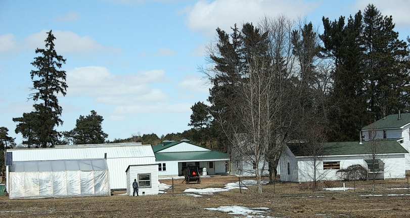 My single Wisconsin Amish photo during our most recent trip shows and Amish buggy in a farmyard and an Amish teen standing next to a small outbuilding.