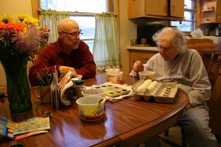 My husband and mom dye eggs at her kitchen table Saturday evening.