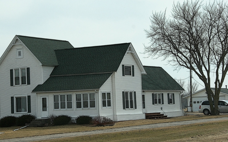 A well-kept farmhouse between Redgranite and Omro, Wisconsin, has likely evolved through the years with numerous additions.