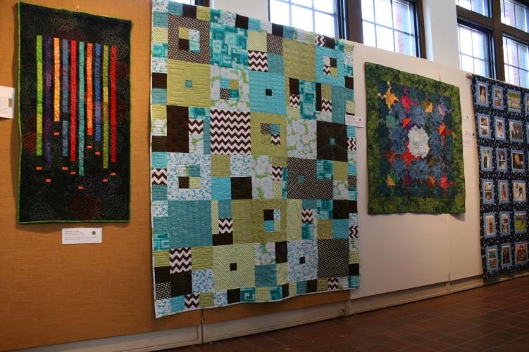 Quilt art lines a hallway.