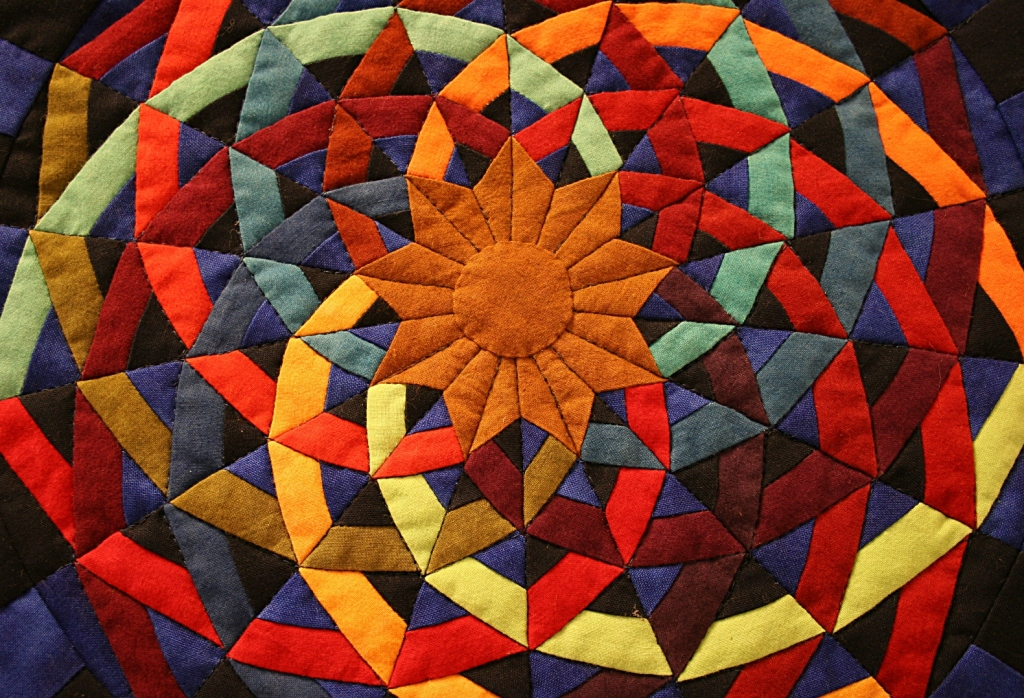 A quilted work of art bursts with color.