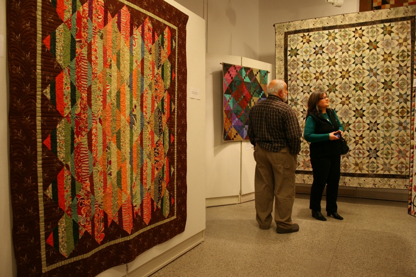The quilter's husband and the quilter view the extensive collection of quilts.
