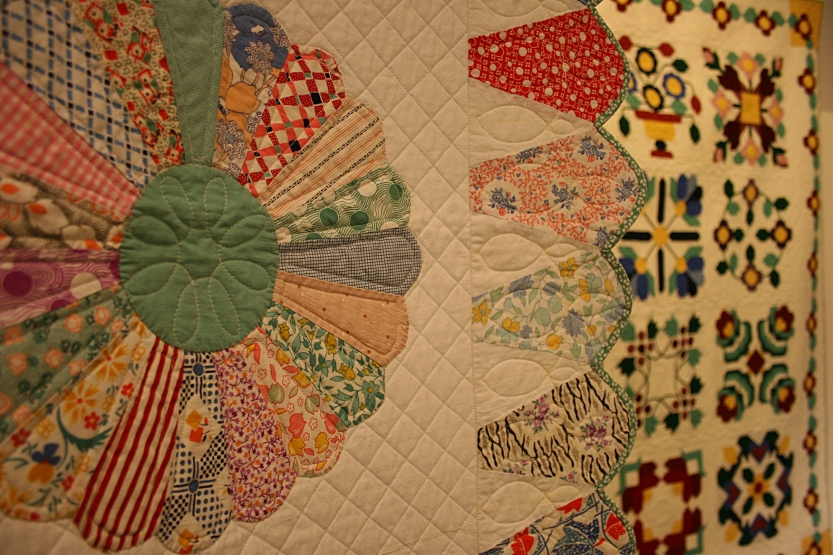 A close-up of the traditional Dresden Plate pattern in the foreground with a second quilt in the background.