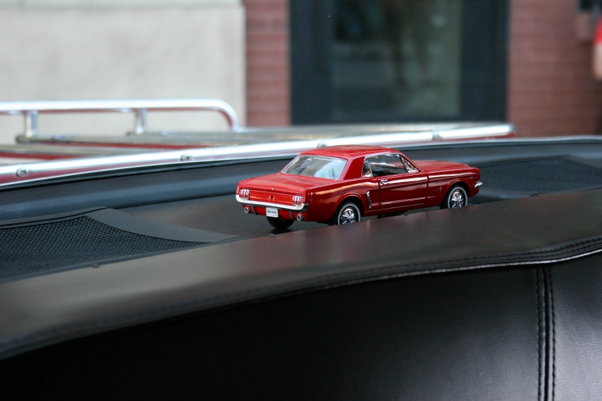 Details: a toy Mustang in a rear window.