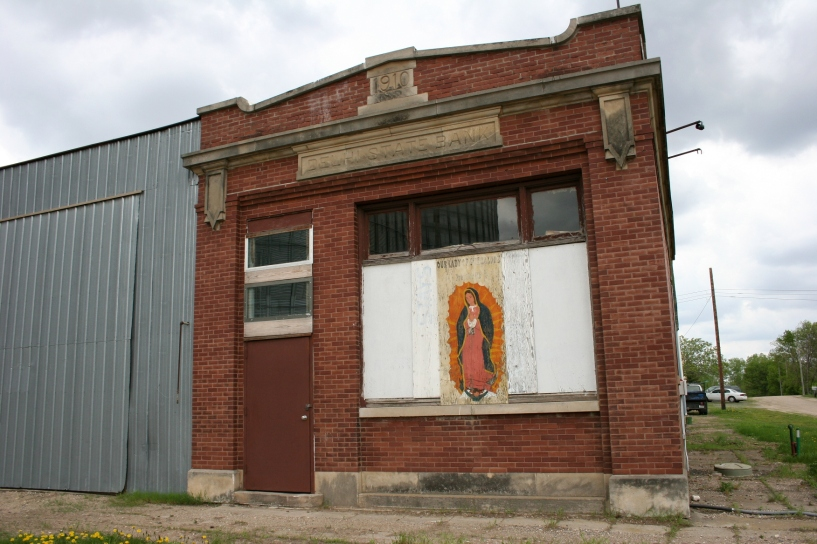 The front window of the 1910 Delhi State Bank is now mostly boarded with a painting of Our Lady of Guadalupe.