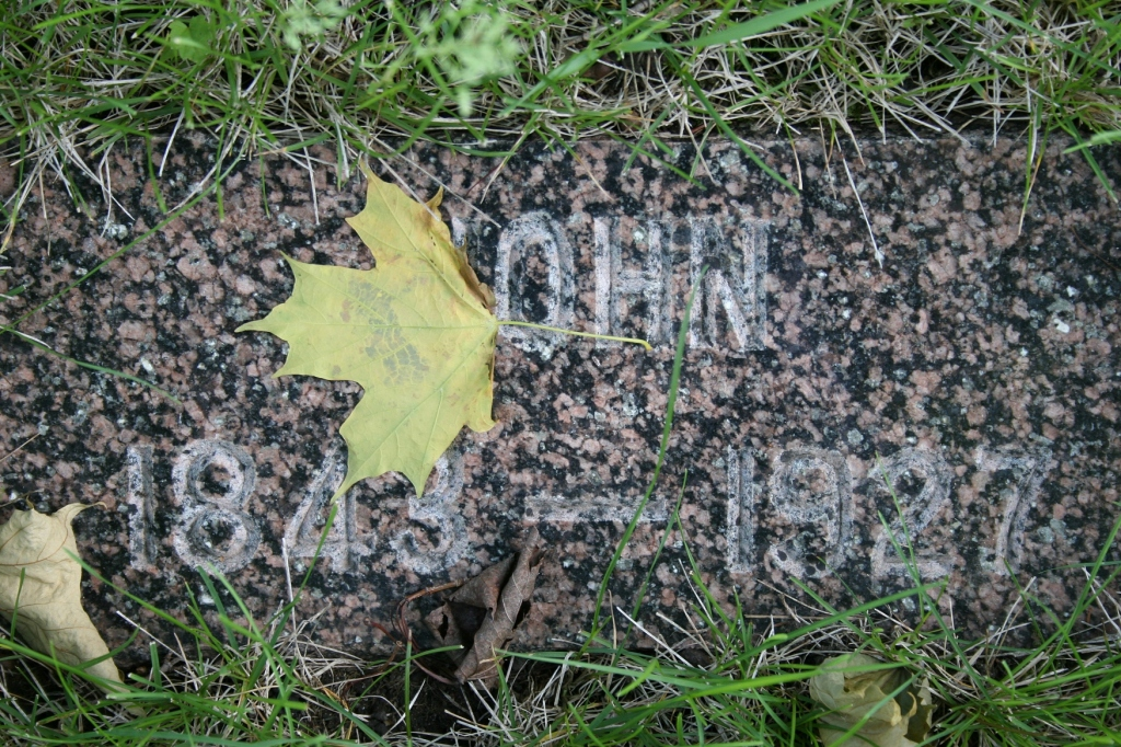 Nature leaves her signature on an in-ground grave marker.