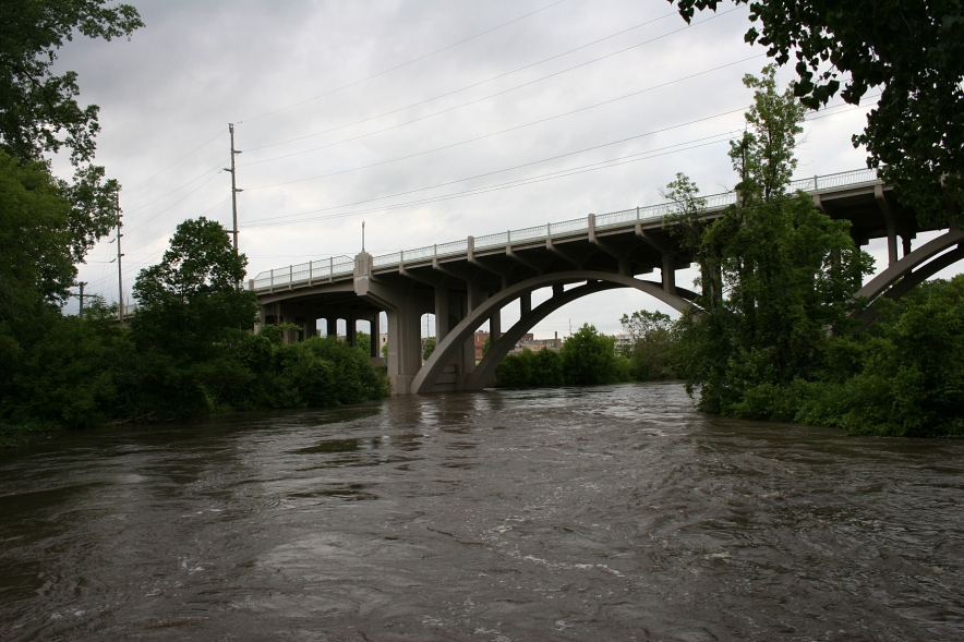 The Straight River has flooded Teepee Tonka Park and churns here toward the Highway 60 viaduct connecting the east and west sides of Faribault.