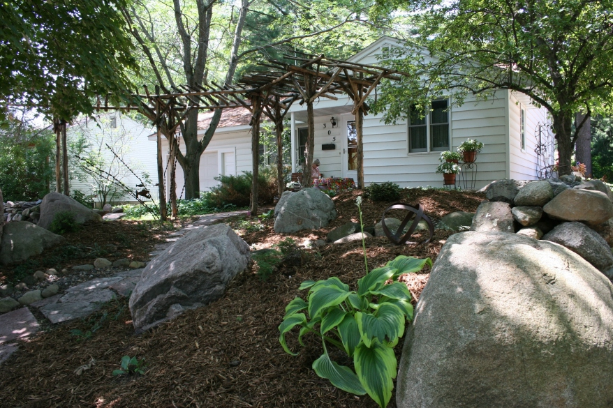 A rustic arbor and rocks define the front yard created by Switzer Landscaping.