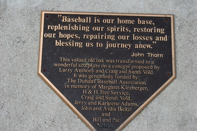 This plaque, by a baseball player sculpture at Memorial Park in Dundas,