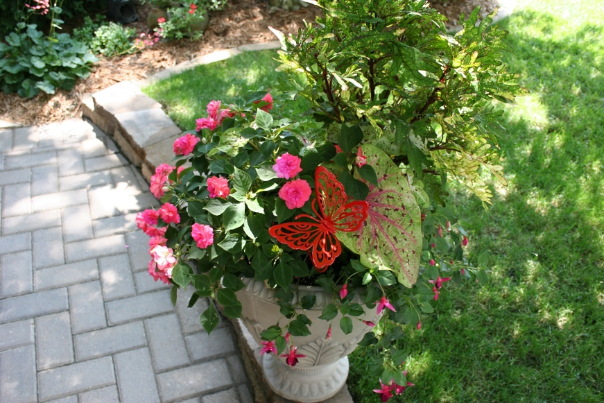 Impatiens and butterfly art add color to a plant situated along a walk way.
