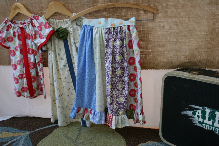 Some of Derrin's creations displayed next to a vintage suitcase in the porch.