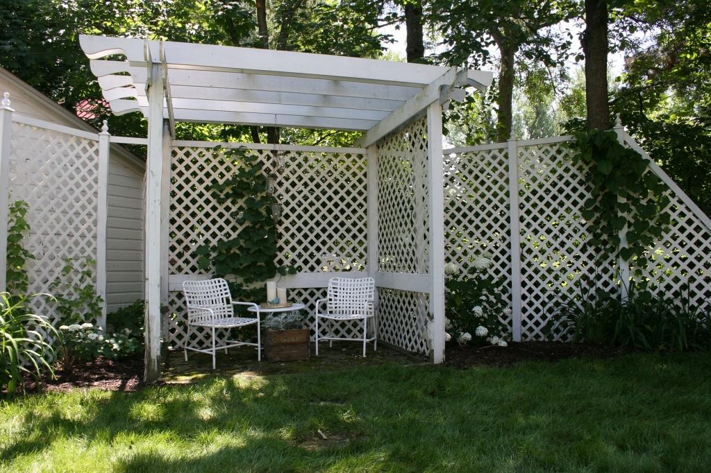 Latticework accents a corner garden pergola.