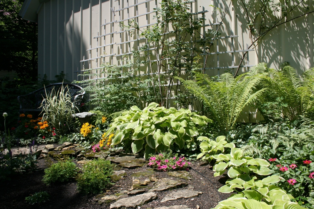An inviting spot, complete with trellis, to sit a spell next to the garage.