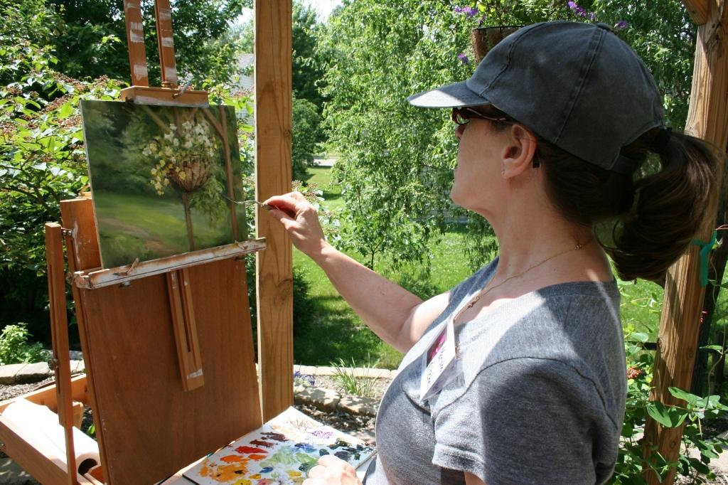 Artist Marsha Kitchel paints on the patio.