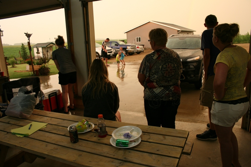Gathering inside the garage to watch the kids playing in the rain.