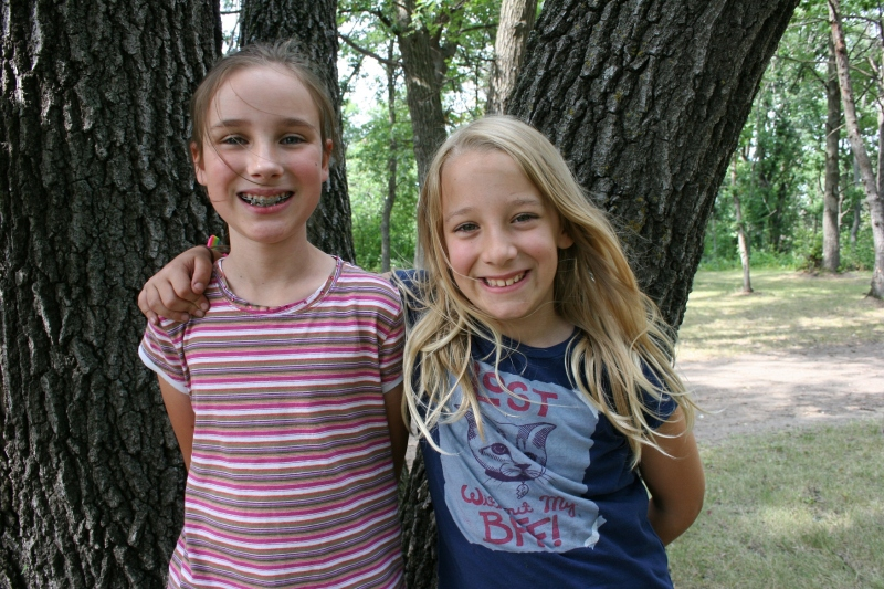 Cousins Beth, left, and Keira paused for a photo as they scampered through the woods looking for a tree to climb. They never found one they could both ascend.