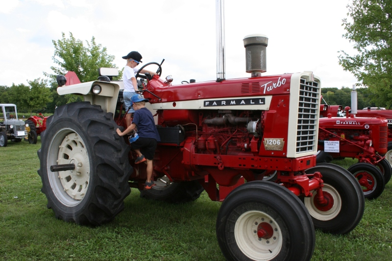 Brothers William and Jacob climb atop a Farmall.
