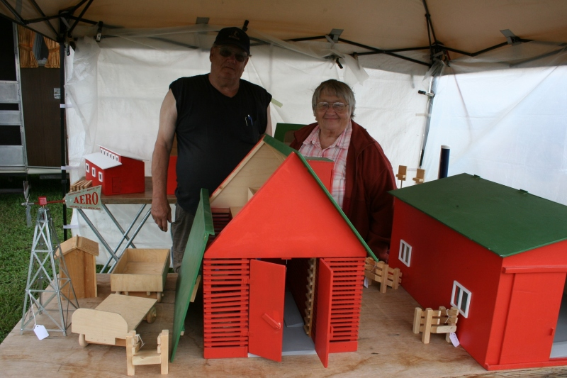 Al and Marllene Sutherland of Country Junction, Tripoli, Iowa, pose with the replica small scale farm buildings Al constructs from memory. The corn crib in the foreground includes 400 pieces and sells for $200.