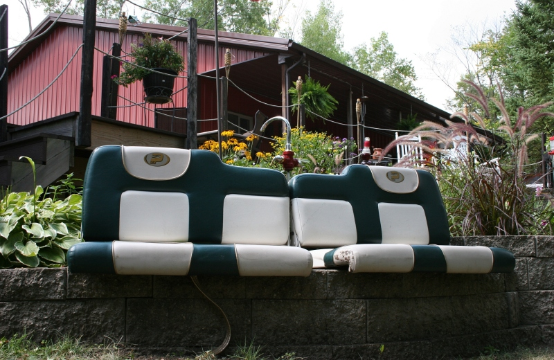 Boat seats repurposed as a seating area on a retaining wall.