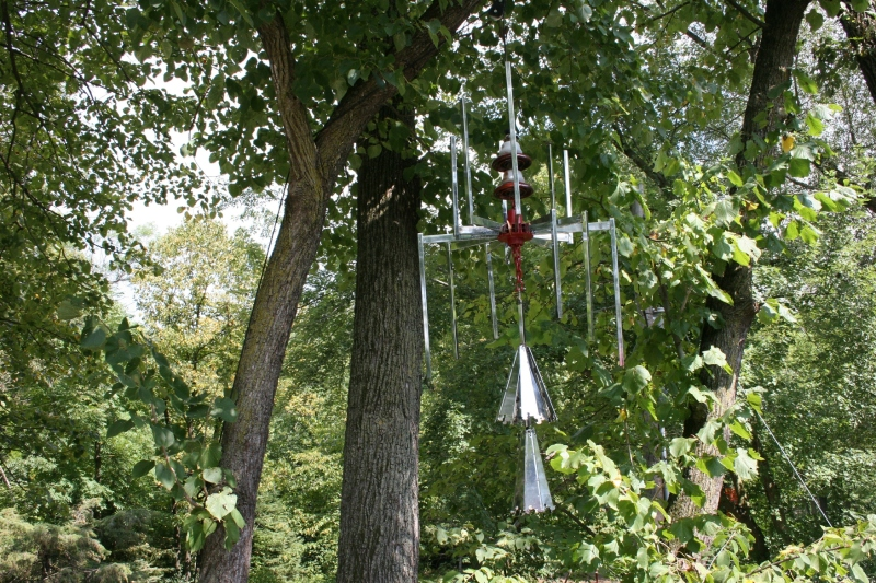 Oversized chimes crafted from discarded clothing racks (etc.) and strung high in a tree.