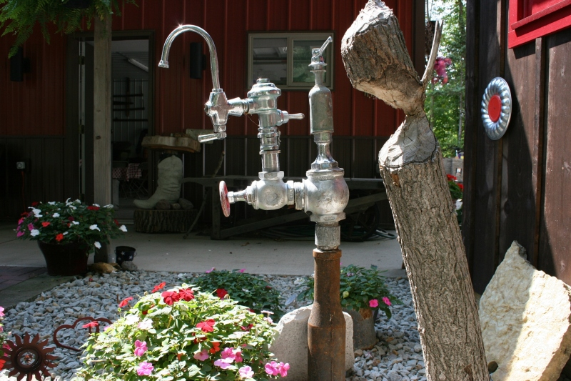 Discarded plumbing provides materials for art in a flower garden.