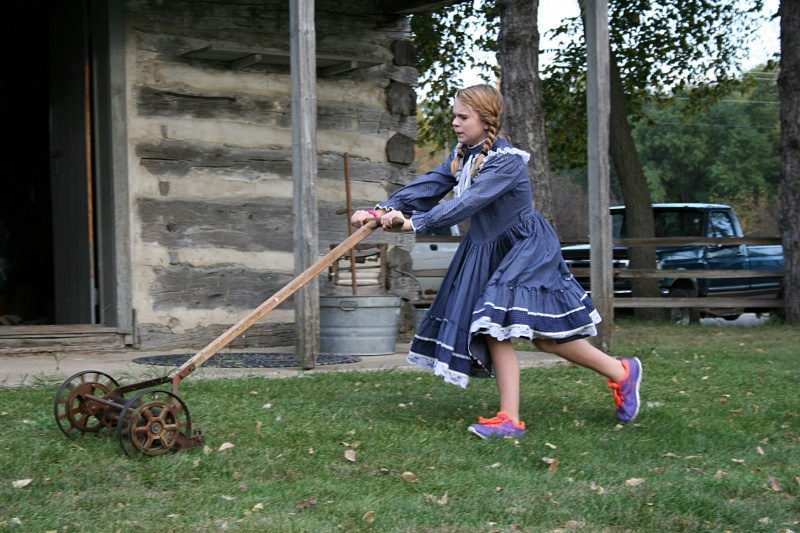 Kaylee, role-playing Katie, struggles to push an old-fashioned lawnmower across the lawn outside the log cabin.
