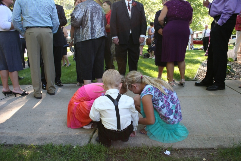 Two wedding guests and ringbearer Hank gathered on the church sidewalk next to the receiving line.