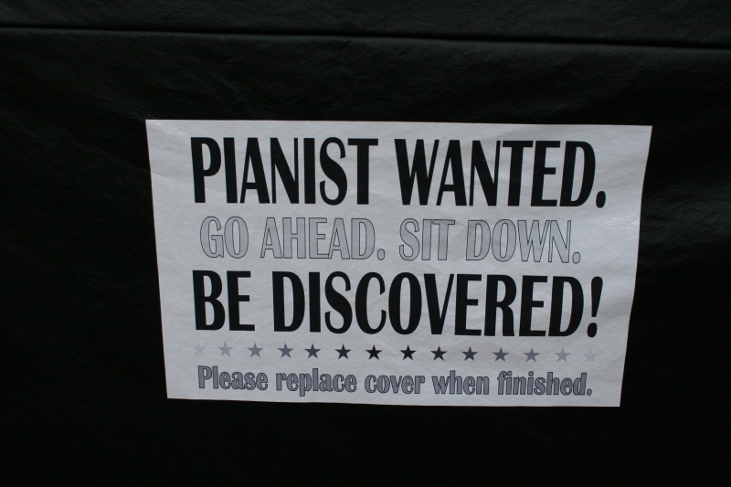 A sign invites pianists to sit down and play.
