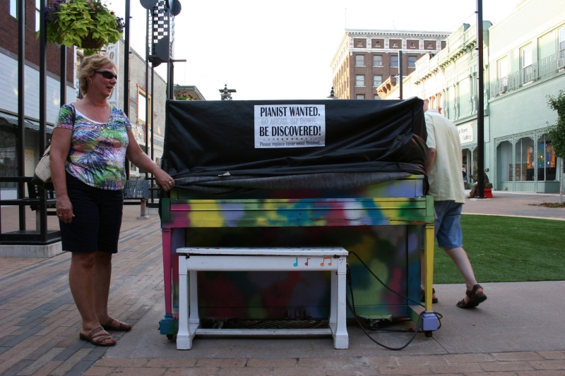 Beth Ann and Randy uncover the Plaza piano, revealing a color piano which mimics my friend's colorful shirt.