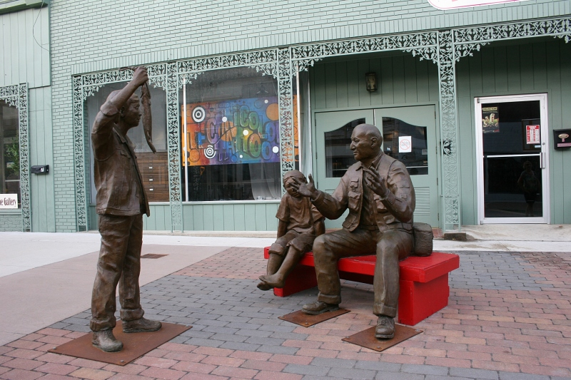 "Sculptor Martha Pettigrew's ""Fish Story,"" featuring a grandfather and two of his grandchildren, has been purchased as a permanent part of the city's sculpture collection. The red bench was recently replaced by a gray bench."
