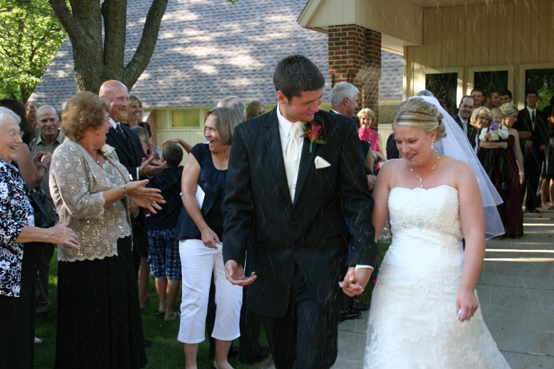 Guests shower Jared and Carlyn with birdseed as they leave the church.