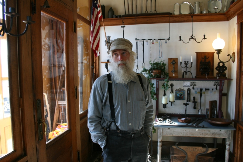 Blacksmith Tom Latane talks about his craft  in the front part of his shop. Behind him are examples of his work.