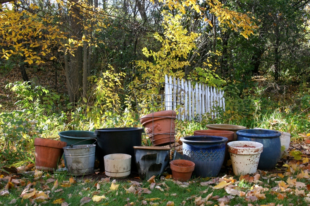 Flower pots are stacked, waiting to be stashed inside the garage.