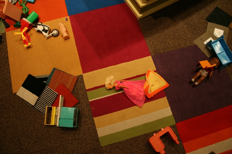 Toys strewn across the floor in a play area of the 1970s part of the exhibit.