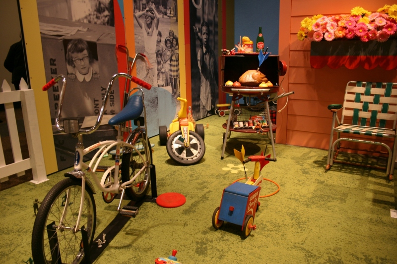 Outdoor toys and a play area are part of the exhibit.