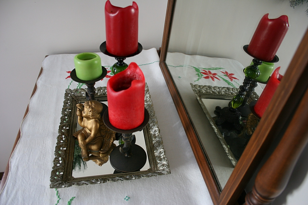 Around the corner on a vintage dresser from my husband's family, I display candles and an angel on a vintage mirrored tray set atop a vintage holiday linen.